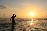 Fototapeta Zachód słońca - The figure of a woman on the sea with a high wave and spray on the background of a golden sunset. © Viaceslav