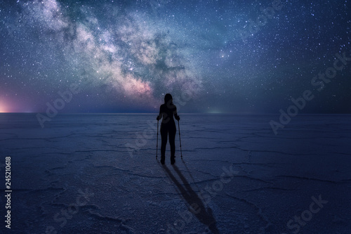 Milky Way with silhouette of a standing woman on the desert land. Scenery landscape with night starry sky and silhouette of standing woman. Milky Way Galaxy with traveler.