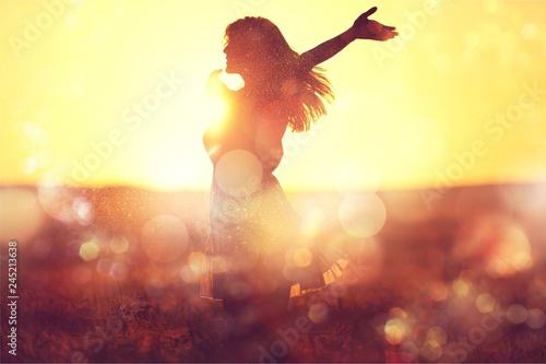 Leinwandbild Motiv Young woman on field under sunset light