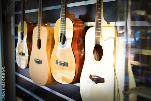 Spanish acoustic guitars hanging on the wall at a music store. - 245250642