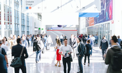 crowd of trade fair visitors walking in a clean futuristic corridor