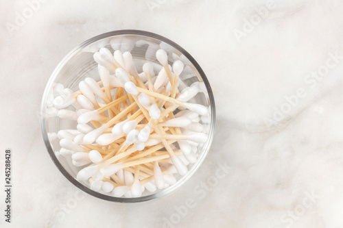 An overhead photo of bamboo cotton swabs in a glass jar on a marble surface with a place for text