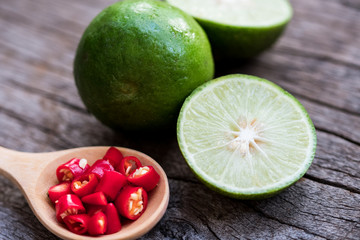 bowl of red chili peppers and green lime on the wooden background.