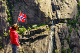 Tourist woman with norwegian flag in rocks mountains