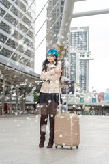 Travel tourist standing with luggage waiting to pick up her family at the airport. Travel woman at international airport while standing cooling snow falling. Female passenger at terminal,outdoors.