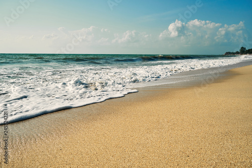 Wild sandy beach with surf. Blue sky in the background - 245324221