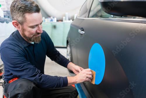 Mann bringt einen Aufkleber mit dem Firmenslogan auf einem Auto an