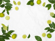 limes and green leaves on white crumpled background