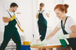 Smiling woman with gloves and spray wiping table while cleaning interior with crew