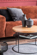black fancy vases on round wooden coffee table in front of brown velvet settee