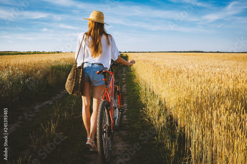 Foto Murales Girl in wheat summer field with bicycle