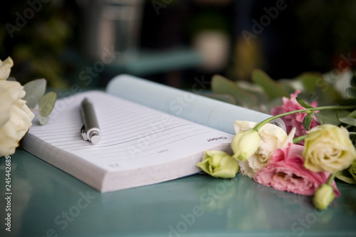 Order book and pen lying on counter of florists shop © flairimages