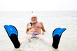 Leinwandbild Motiv Senior man on beach vacation snorkel and flippers relaxing in sea smiling at camera