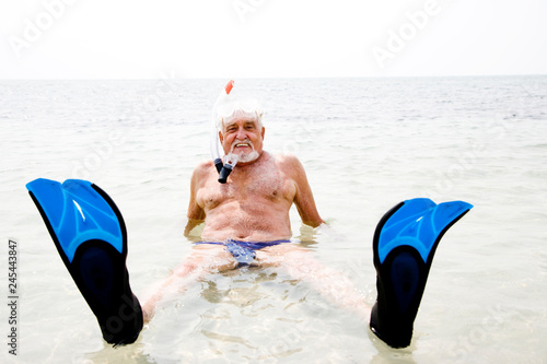 fototapeta na ścianę Senior man on beach vacation snorkel and flippers relaxing in sea smiling at camera