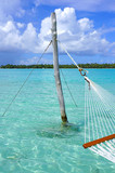 Hammock with a view, planted in the azure waters of the Bora Bora lagoon, French Polynesia