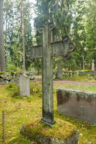 Cross at old semetery in Finland with grave crosses and stones.