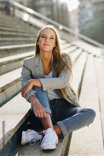 Beautiful young blonde woman sitting on urban steps.
