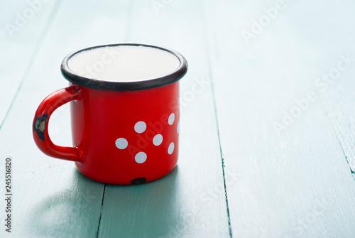 milk in dotted enamel mug, blue wood background