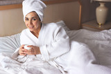 Young beautiful woman in white bathrobe lying in bedroom with cup of hot coffee. Relax in the morning or after work - 245537468