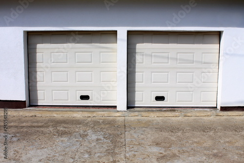 Two Modern White Rollup Garage Doors With Cracked Concrete Driveway