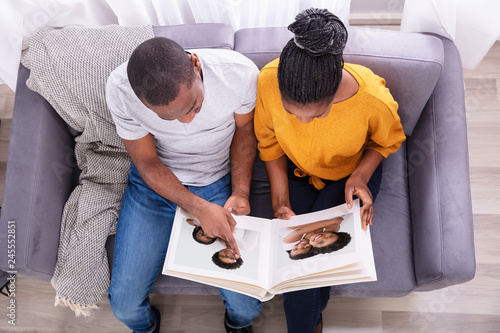 High Angle View Of A Couple Looking At Photo Album - 245552851
