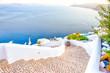 Leinwandbild Motiv Travel Destinations.Picturesque Cityscape of Oia Village in Santorini with Volcanic Caldera and sailing Boats on Background.