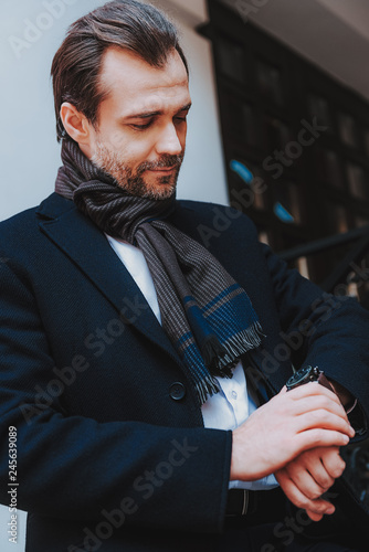 Foto Murales Trendy businessman in black coat is checking time
