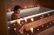 Young lady take relaxed spa bath with candle
