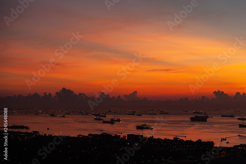 Dawn on the background of the sea with boxes of barges in Singapore