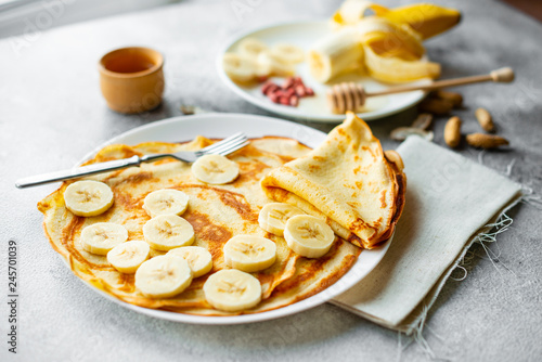 Foto Murales Food, dessert, pastries, pancake, pie. Tasty beautiful pancakes with banana and honey on a concrete background