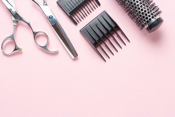 Scissors and comb on a pink background, copy space