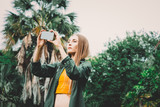 Young blond woman on vacation take picture with smartphone in the park. - 245702030