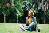 Young blond woman on vacation is sitting in the park searching information on smartphone. - 245704605