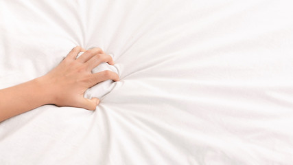 Female hand grasping white crumpled bed sheet