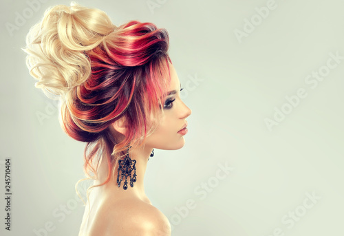 Leinwandbild Motiv Beautiful model girl  with elegant  multi colored hairstyle . Stylish Woman with fashion  hair  color highlighting.   Creative  red and pink roots ,   trendy  coloring.