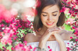 Beauty portrait of young woman closeup. Attractive female in flowers with copy space. Beautiful lady outdoor.