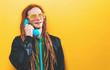 Dreadlocked man talking on old fashioned retro phone