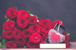 Concept of a gift for Valentine's Day.  large bunch of red roses and an open box with a stylish, knitted heart
