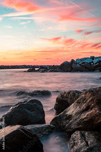 sunset at sea with rocks in the foreground
