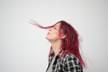 The girl in a plaid gray shirt on a white background with dyed red hair. © spaskov
