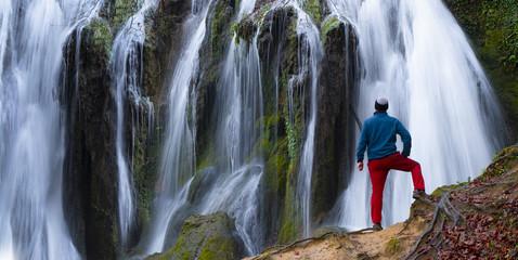 Single man standing near waterfall.