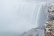 Scenic view of Horseshoe Falls on Niagara river in Canada. Beautiful depressive winter look of largest cascade of famous Niagara falls from Canadian side of border. Rocks are covered by ice and snow