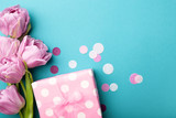 Gift box wrapped in polka dot paper and pink tulip flowers on blue background decorated with confetti. Top view, flat lay.