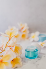group of skincare products including moisturiser and scrub pots on marble table with exotic frangipani flowers © faithie