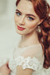 Close up portrait of young ginger bride with freckles in fashionable wedding dress