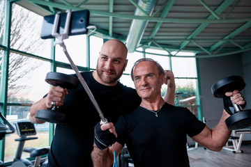 two friends athletes takes a selfie while lifting dumbbells