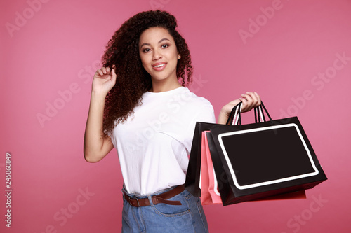 Portrait of an excited young african woman holding shopping bags and showing credit card isolated over pink background - 245860849