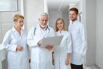 Portrait of fout doctors talking in white uniform.