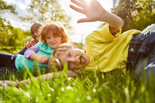 Leinwanddruck Bild Kinder spielen und albern herum auf einer Wiese