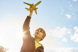 Junge beim Spielen mit Flugzeug in der Hand - 245884250